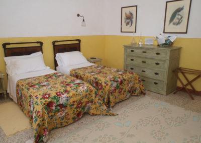 Camera-gialla_letti stanza in stile rustico